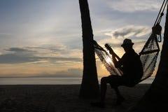 Sirva tocar la guitarra en la playa con puesta del sol fotos de archivo