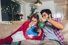 Sirva tomar cuidado de su novia enferma que miente en el sof? fotos de archivo libres de regalías