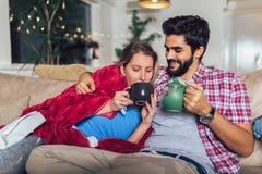 Sirva tomar cuidado de su novia enferma que miente en el sof? imagenes de archivo