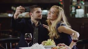 Sirva tomar el selfie con la mujer y ellos que se besan en mejillas almacen de video
