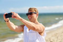 Sirva tomar el selfie por smartphone en la playa del verano Foto de archivo