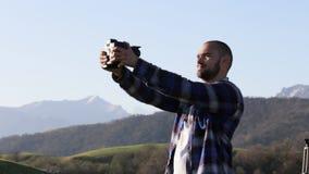 Sirva tomar la foto del selfie con la cámara profesional de la película en el paisaje de la montaña almacen de video