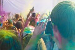Sirva tomar la foto en el teléfono móvil en festival del color del holi Fotografía de archivo