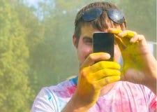 Sirva tomar la foto en el teléfono móvil en festival del color del holi Fotos de archivo
