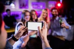 Sirva tomar la fotografía de sus amigos con el teléfono móvil Imagen de archivo libre de regalías