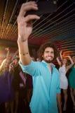 Sirva tomar un selfie del teléfono móvil mientras que los amigos que bailan en sala de baile Fotos de archivo