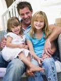 Sirva y dos chicas jóvenes que se sientan en la sonrisa del patio imagen de archivo