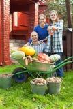 Sirva y dos mujeres con las verduras en jardín Fotos de archivo