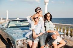 Sirva y dos mujeres hermosas que se unen cerca del coche del vintage Imagen de archivo