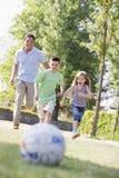 Sirva y dos niños jovenes al aire libre que juegan a fútbol Imágenes de archivo libres de regalías