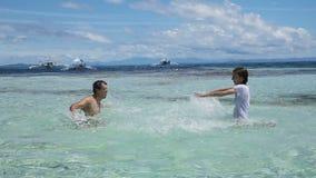 Sirva y su hija que salpica el agua en el mar almacen de metraje de vídeo