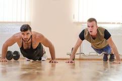 Sirva y su instructor personal que ejercita tirón-UPS en el gimnasio Técnica de ejercicios atleta del novato con el coche Fotos de archivo libres de regalías