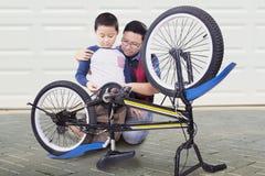 Sirva y su reparación del hijo una bicicleta en casa Foto de archivo libre de regalías