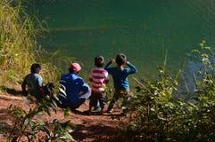 Sirva y sus niños que se sientan por la Laguna Esmeralda en Chiapas Foto de archivo libre de regalías