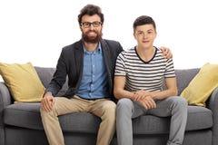 Sirva y un adolescente que se sienta en un sofá Imagenes de archivo