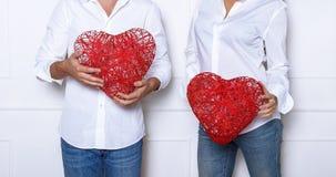 Sirva y una mujer que lleva a cabo corazones de mimbre rojos Imagenes de archivo