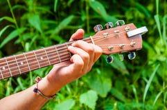 Sirve el acorde E de la tenencia de la mano en un fretboard de madera del cuello de la guitarra acústica en fondo verde escénico  foto de archivo
