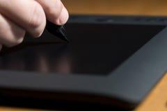 Sirve el dibujo de la mano en una tableta de gráficos de ordenador foto de archivo libre de regalías