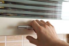 Sirve la mano abren las puertas del armario de la cocina, cierre Fotos de archivo libres de regalías