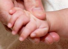 Sirve la mano del bebé de la explotación agrícola de la mano Imagen de archivo libre de regalías
