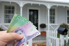 A sirve la mano lleva a cabo billetes de dólar de NZ contra un frente de Ameri del norte Imagenes de archivo