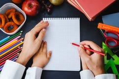 Sirve la mano que lleva a cabo una mano de los childs con el lápiz Concepto de la escuela Imagenes de archivo