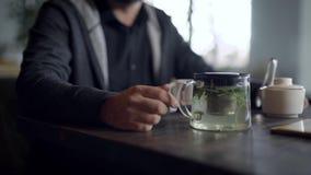 Sirve las manos y la taza de cristal de infusión de hierbas de la medicina metrajes