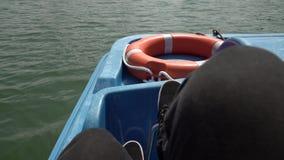Sirve los pies que hacen girar pedales en la bicicleta del agua en un lago Barco de giro para los turistas, actividad del verano  metrajes