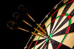 Sisal dartboard with three darts in a bullseye Royalty Free Stock Photos