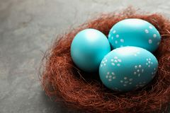 Sisal nest with painted Easter eggs on color background, closeup. Space for text royalty free stock images