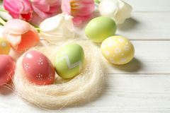 Sisal nest and painted Easter eggs on table, space for text. Sisal nest and painted Easter eggs on wooden table, space for text royalty free stock photography