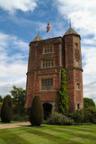 Sissinghurst Castle Tower White Clouds Blue Sky Background. Sissinghurst Castle Tower on a white clouds and blue sky background in a green lawn Royalty Free Stock Photo