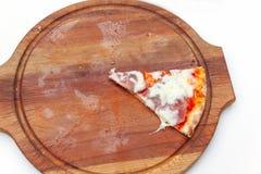 Sista en skiva av läcker italiensk pizza med skinka och ost på träbräde på den vita tabellen Pizzatid Top besk?dar N?rbild royaltyfria foton