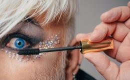 sista touch Manlig ögonmakeup för mode Transgender mannen för att applicera mascara Manliga för Transgender för makeupkonstnär ög arkivbilder