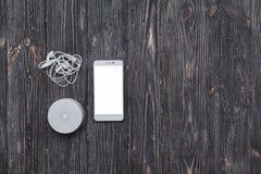 Sistema acustico portabile con le cuffie e lo schermo in bianco del telefono cellulare sulla tavola di legno scura fotografie stock