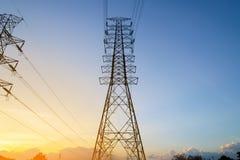 Sistema ad alta tensione del pilone di elettricità al tramonto Fotografia Stock