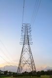 Sistema ad alta tensione del pilone di elettricità al tramonto Fotografia Stock Libera da Diritti