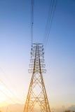 Sistema ad alta tensione del pilone di elettricità al tramonto Fotografie Stock
