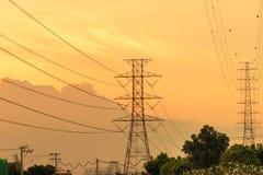 Sistema ad alta tensione del pilone di elettricità al tramonto Fotografie Stock Libere da Diritti