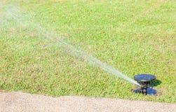 Sistema antincendio dell'acqua che innaffia sull'erba verde fresca. fotografia stock