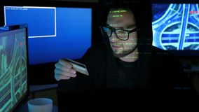 Sistema bancario que se agrieta del pirata informático criminal, pirata informático que usa el ordenador portátil, ordenadores pa almacen de metraje de vídeo