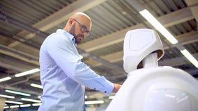Sistema cibernético hoy Tecnologías robóticas modernas Robot autónomo del Humanoid un hombre que usa su pantalla táctil De alta t almacen de video