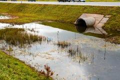 Sistema concreto del agujero del tubo de la alcantarilla que drena el agua de aguas residuales cerca de imagen de archivo libre de regalías