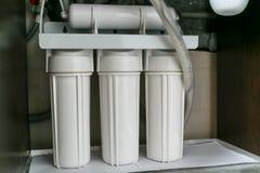 Sistema da purificação de água da osmose reversa em casa A instalação de filtros da purificação de água sob a banca da cozinha no foto de stock royalty free