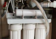 Sistema da purificação de água da osmose reversa em casa A instalação de filtros da purificação de água sob a banca da cozinha no imagens de stock royalty free