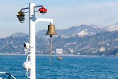 Sistema de alarme na plataforma do navio - lâmpadas de luzes de sinal e o sino de bronze contra o fundo do mar e das montanhas Imagens de Stock