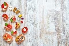 Sistema de aperitivos/de bocados/de tapas en una tabla de madera Fotos de archivo