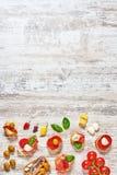 Sistema de aperitivos/de tapas españoles en una tabla de madera vertical Imagen de archivo