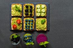 Sistema de bocadillos vegetarianos de la tostada con el aguacate y las bebidas Variedad de comida y de bebidas sanas Foto de archivo