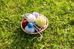 Sistema de bolas y de agujas coloreadas del hilado en la placa de la paja Imagen de archivo